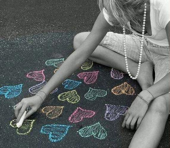 Une fille dessine des coeurs à la craie sur le sol.