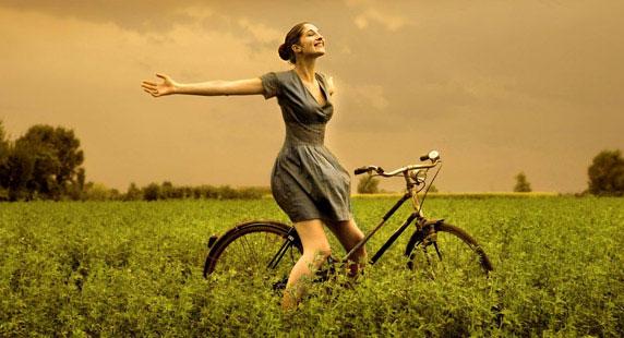 Image d'une femme heureuse, sur le terrain, avec son vélo
